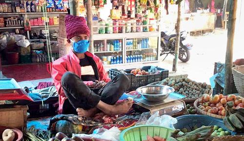 A shopkeeper in Bangladesh wearing a mask provided as part of the study. Photo: IPA-Bangladesh.