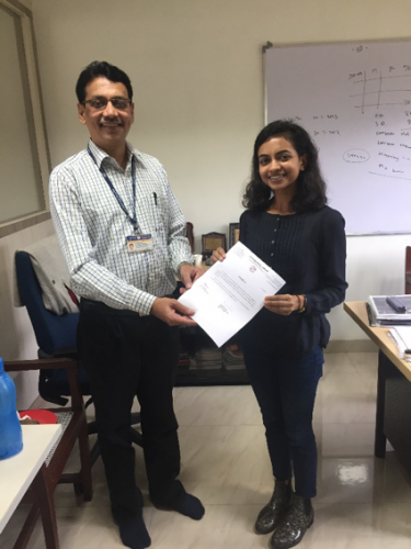 Dr. Atul Budukh presents Krisha with her certificate of completion from Tata Memorial Center.