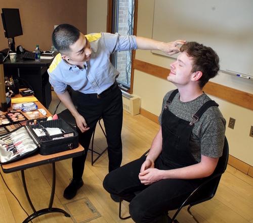 Kodo Nishimura applies make up to a student.