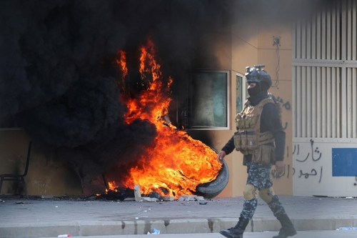 A member of Iraqi security forces walks past the U.S. Embassy in Baghdad, Iraq, January 2020 (Thaier Al-Sudani / Reuters)