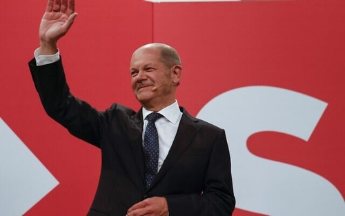 SPD leader Olaf Scholz greeting celebrating party members Sunday evening.