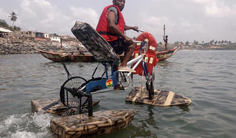 A rider tests out a water cycle with paddles invented by inventor Frank Darko