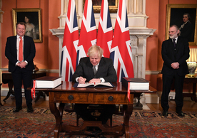 British Prime Minister Boris Johnson signing the UK-EU Trade and Cooperation Agreement as Lord David Frost, UK chief negotiator, and Sir Tim Barrow, UK ambassador to the EU, look on, December 30.