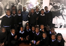 "Seth Mazibuko with a group of student visitors. The young man smiling in the photograph behind him is Seth's 17-year-old self, greeting supporters at his trial for ""sedition and terrorism."""