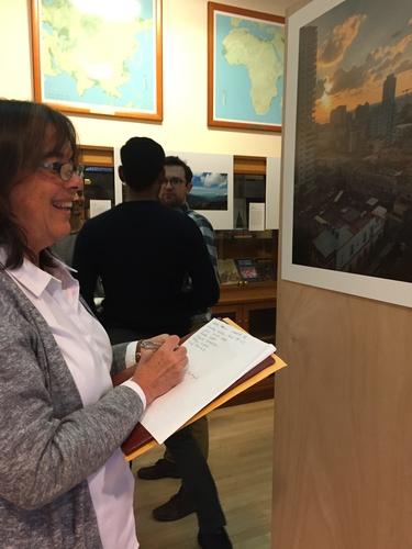 Professor Claudia Valeggia views each of the photographs in the exhibit.